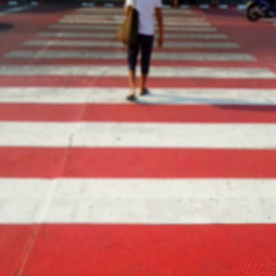 Low section of person walking on red road