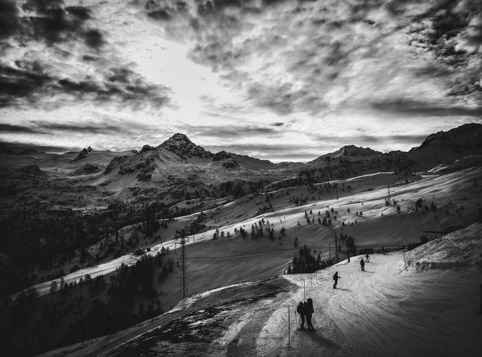 High Angle View Of Silhouette Skiers On Snowcapped Mountain