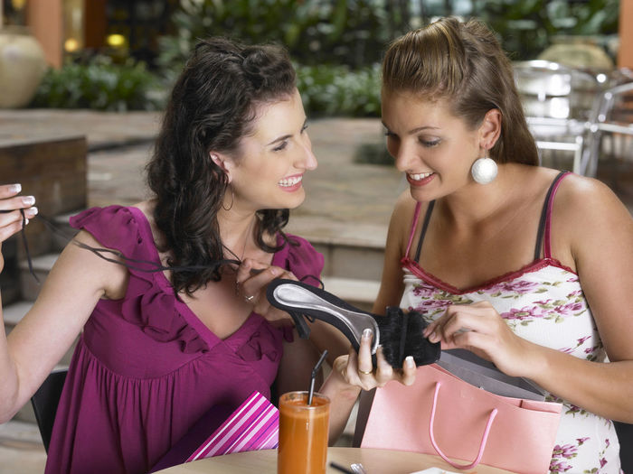 Female Friends Sitting With Gifts At Outdoor Cafe