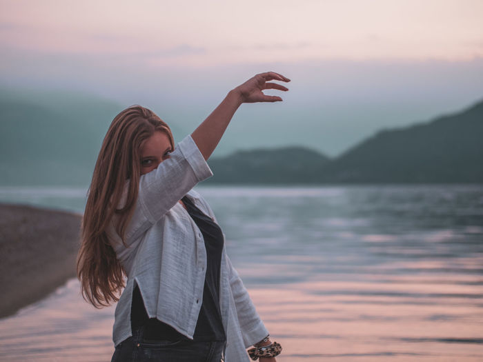 Woman standing by lake against sky during sunset