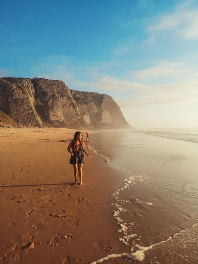 Full length of woman walking on shore against sky