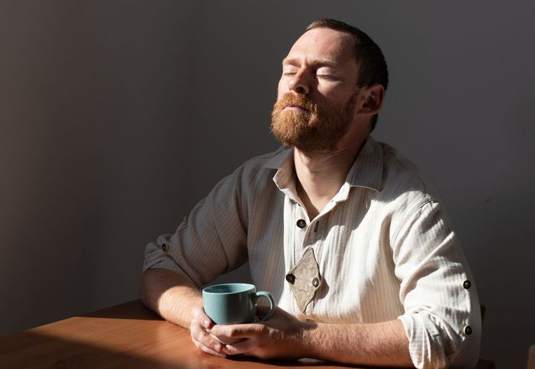 Mid section of man holding coffee cup