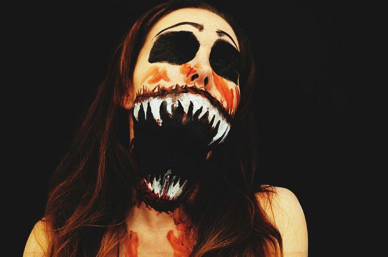 Close-Up Of Woman With Spooky Face Paint Against Black Background