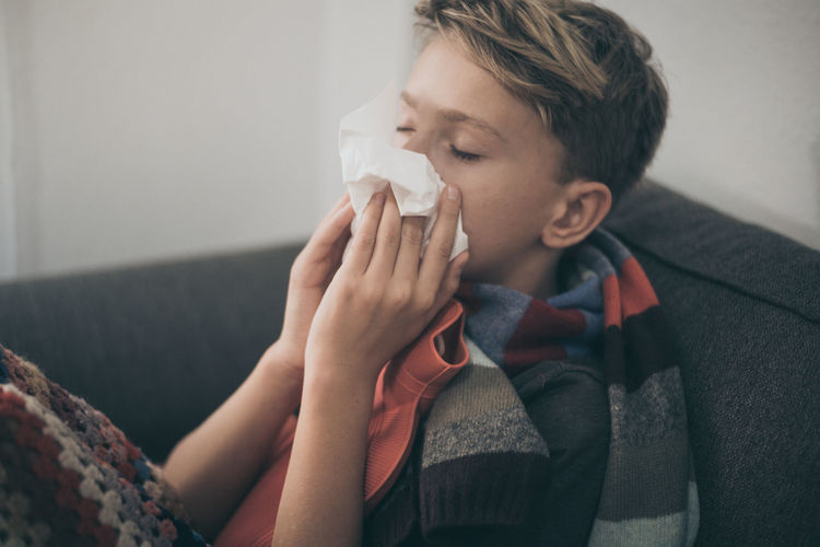 Boy suffering from cold and flu sitting on sofa at home