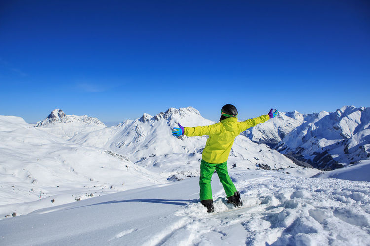 Rear View Of Young Man With Arms Outstretched Standing On Snowcapped Mountain