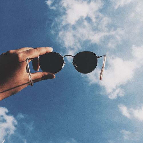 Cropped hand holding sunglasses against blue sky