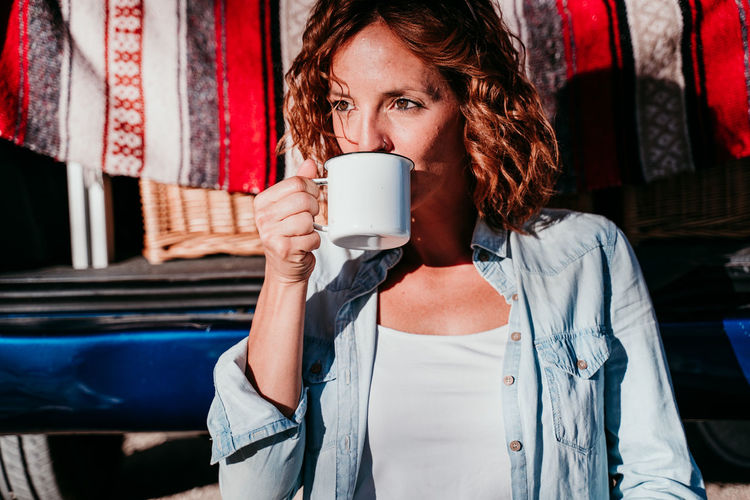 Mid section of woman with coffee cup