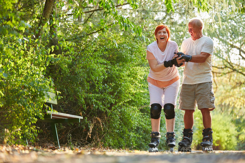 full length of happy man with arms outstretched Active Adult Balance Casual Clothing Couple Couple - Relationship Emotion Environment Exercising Fitness Forest Full Length Fun Happiness Happy Help Hobby Inline Skates Inline Skating Inlineskating Joy Learn Leisure Leisure Activity Lifestyles Males  Man Mature Men Men Movement Nature Old Outdoors Outside People Positive Emotion Practice Retirement Rollerblades Rollerblading Roller-skates Senior Senior Adult Senior Citizen  Senior Citizens Senior Men Seniors Skater Skates Skating Smiling Sport Start Summer SUPPORT Team Together Togetherness Two People Vital Woman