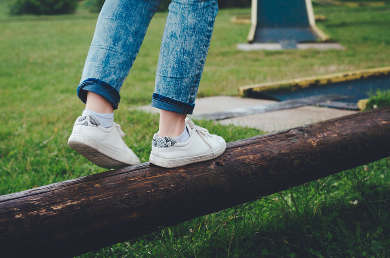 Low section of a girl balancing on a log in white canvas shoes. Blue Color Grass Green Color Textured  Woman Backgrounds Body Part Canvas Shoe Casual Clothing Focus On Foreground Full Frame Girl Human Foot Human Leg Jeans Leisure Activity Lifestyles Low Section One Person Outdoors Real People Standing Summer Yellow Color