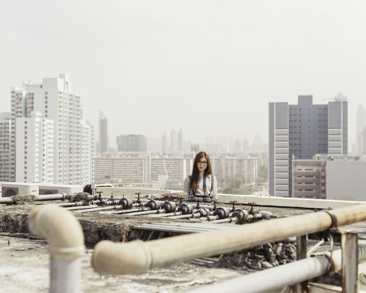 Portrait Of Beautiful Woman Standing By Pipeline On Building Terrace