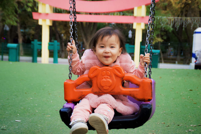 Portrait of cute girl swinging at playground