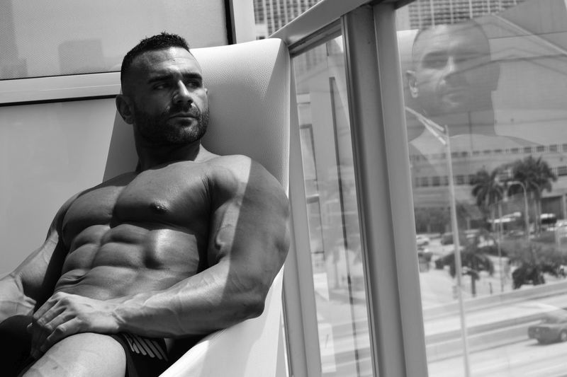 Shirtless muscular man sitting on chair by glass railing in balcony