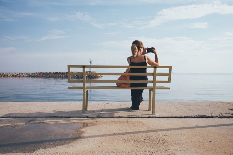 Rear View Of Woman Photographing Through Mobile Phone While Sitting On Bench Against Sea At Beach
