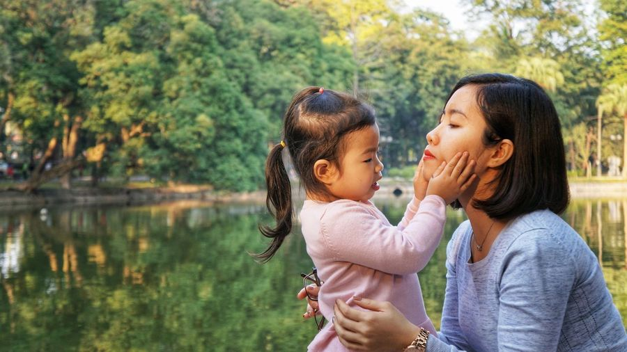 Daughter touching mother cheek at lakeshore against trees