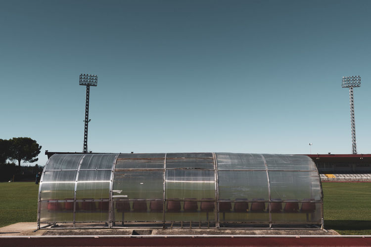 soccer field bleachers from behind Stadium Sport Soccer Bleachers Coach Nature Clear Sky No People Built Structure Seats Playing Field Games Team Sport Competition Match Plastic Floodlight Urban City Football Supporters Grandstand Training Bench From Behind Grass Tree Athletics