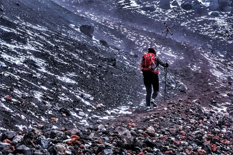 Low angle view of woman hiking on mountain
