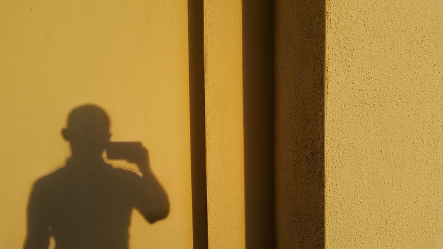 Shadow of man on yellow wall