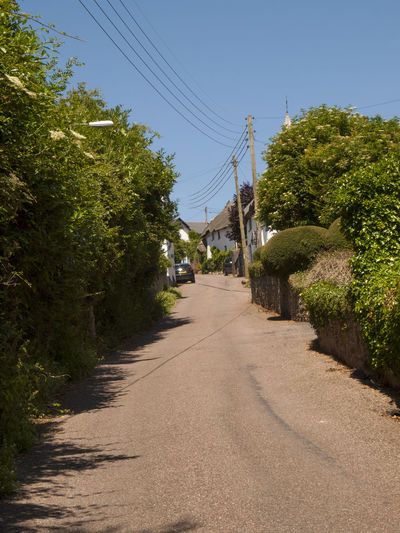 Holcombe Devon England.Holcombe is situated between the seaside resorts of Dawlish and Teignmouth Devon.The village's rich past has been associated with smugglers and been impacted by the growth of the railways - the Bristol to Plymouth main line goes along the coast at Holcombe and is one of the most scenic stretches of the rail network in the country. Smugglers Blue Cable Clear Sky Day Devon Diminishing Perspective Growth Holcombe Mode Of Transport Narrow Nature Outdoors Power Cable Power Line  Road Shadow Sky Street The Way Forward Tourism Transportation Tree Vanishing Point Vivid International