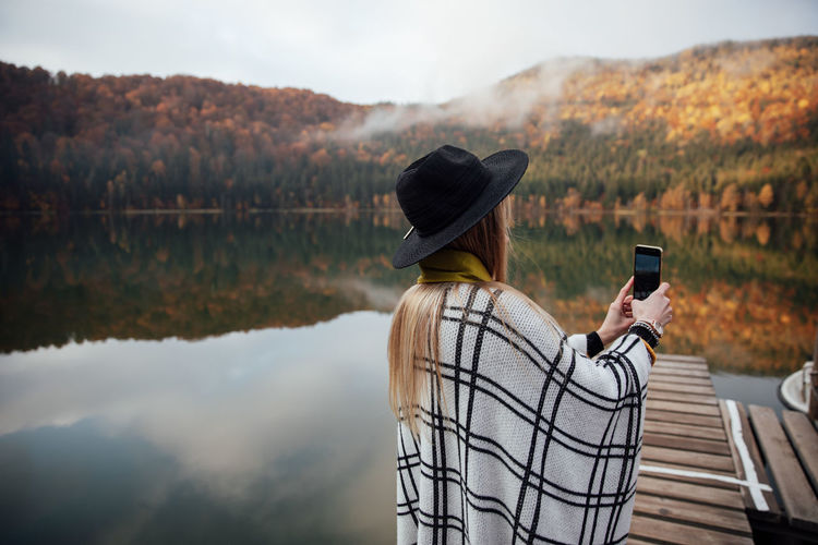 Hipster woman photographs sunset on smartphone. girl holding a mobile phone. autumn background