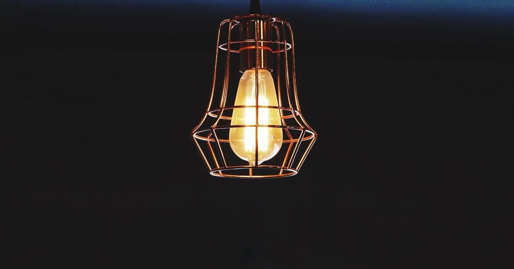 Design lamp with light bulb with dark wall. Illuminated Lighting Equipment Glowing Indoors  Electricity  Copy Space No People Hanging Light Bulb Dark Electric Light Light