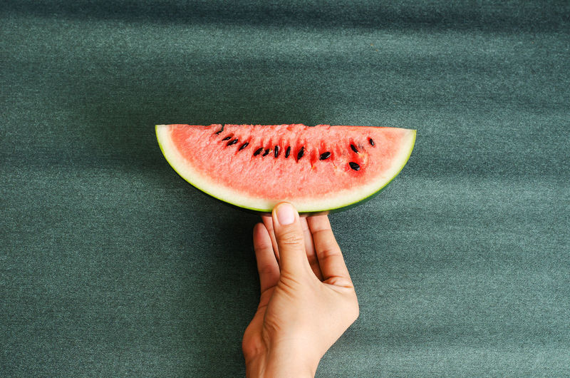 Close-up of hand holding watermelon slice