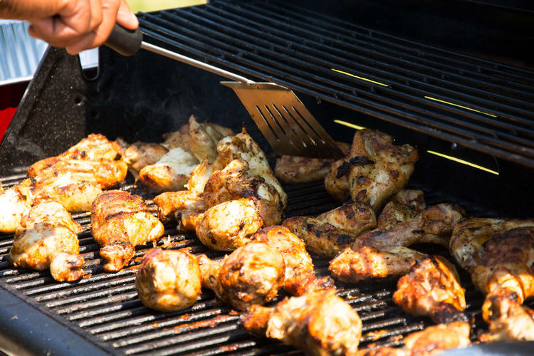 Cropped image of hand roasting chickens in barbecue