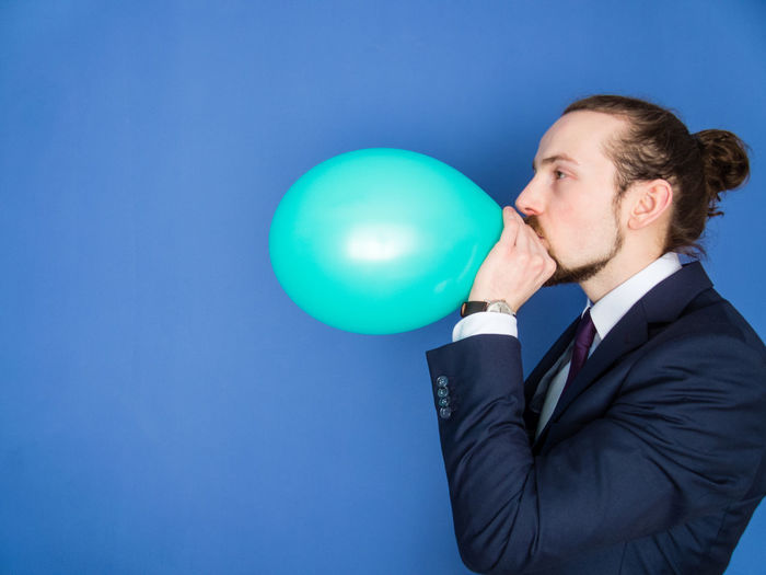 Young businessman blowing green balloon against blue background