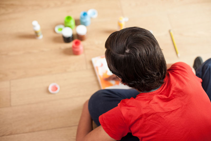 High angle view of boy painting on book at home
