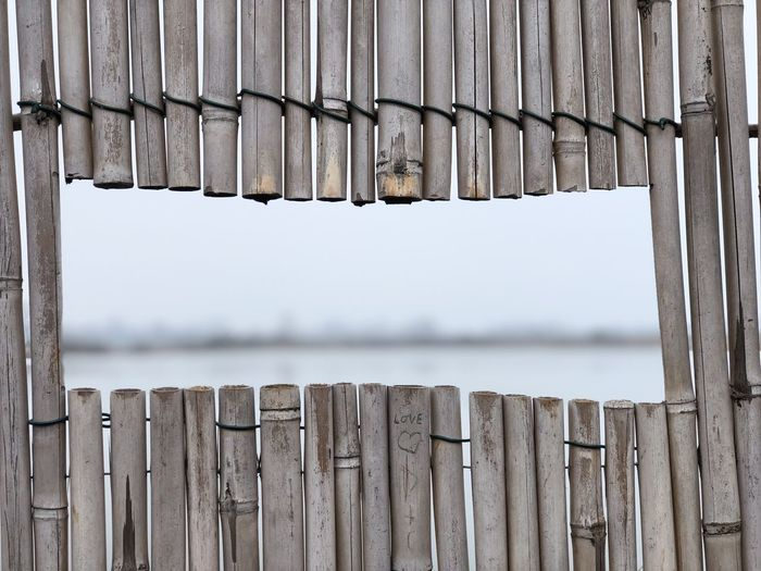 Close-up of wooden fence against lake