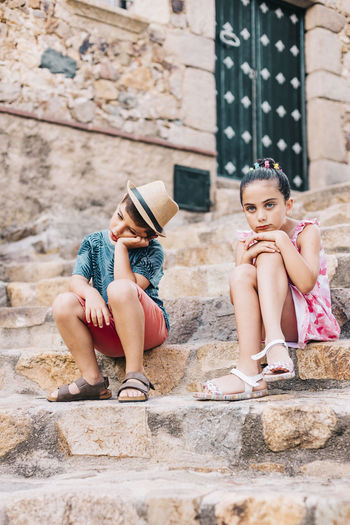 Sad siblings sitting on staircase in city