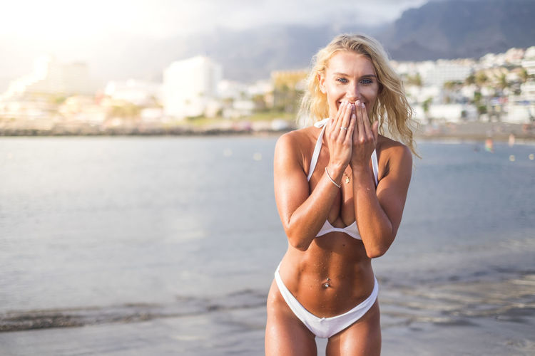 Portrait of smiling woman in bikini standing at sea shore