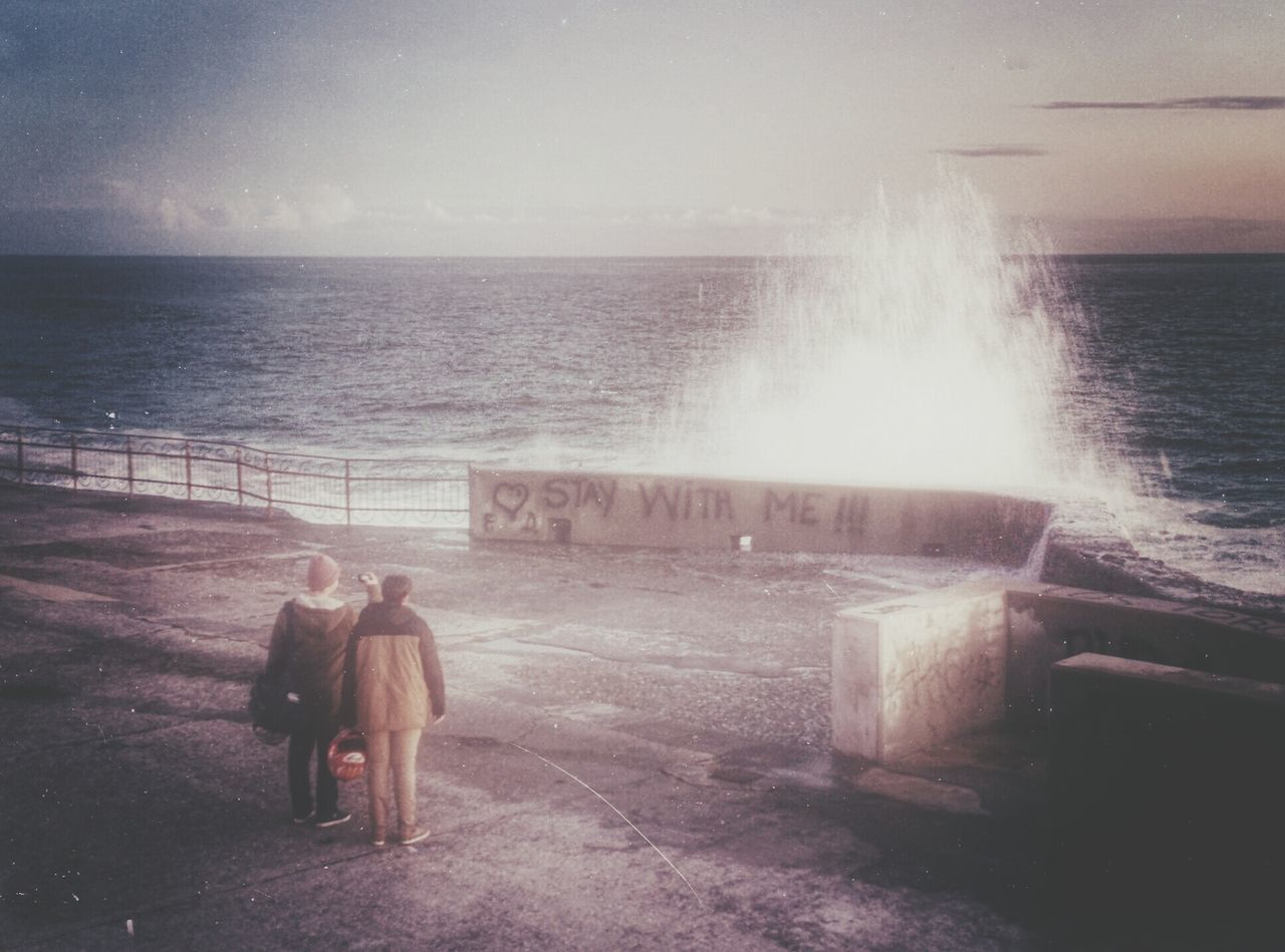Couple photographing rough sea