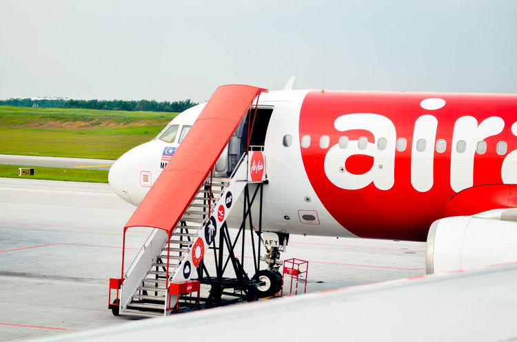 AirAsiaMalaysia AirAsiaThailand AirAsiaZest Airasiaindonesia Air Vehicle Airasia Airasia Malaysia Airasiax Airplane Airport Airport Runway Clear Sky Communication Copy Space Day Land Vehicle Mode Of Transportation Nature No People Outdoors Red Road Sky Transportation Travel White Color