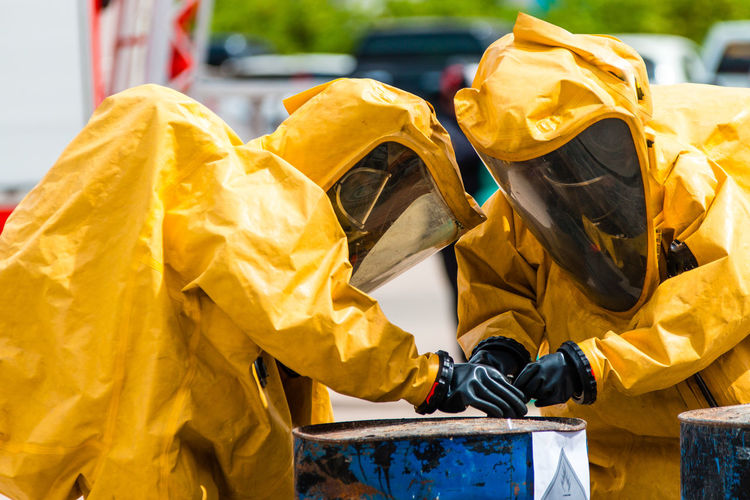 Clothing Day Focus On Foreground Glove Material Occupation Outdoors Paint People Plastic Pollution Protection Protective Glove Protective Workwear Raincoat Safety Security Standing Two People Uniform Working Yellow