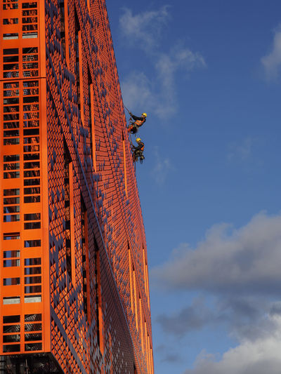 Abseiling workers on a building at Manchester Royal Infirmary wearing matching orange Abseiling Architecture Building Exterior Built Structure Danger Hardhat  Men Orange Color Outdoors Sky Workers Working