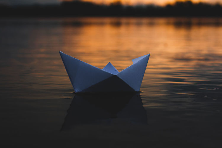 Close-up of paper boat floating on lake during sunset