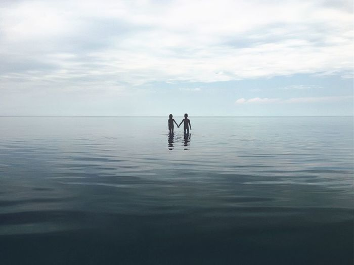 Siblings wading in sea against sky