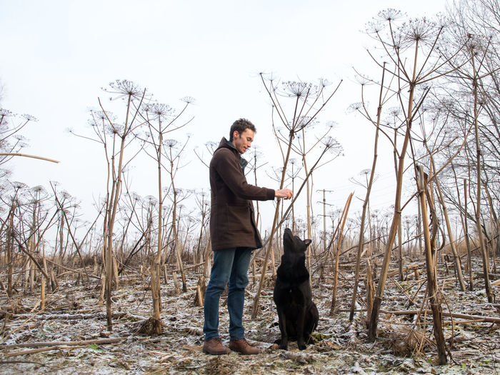 Man playing with dog while standing on land against sky