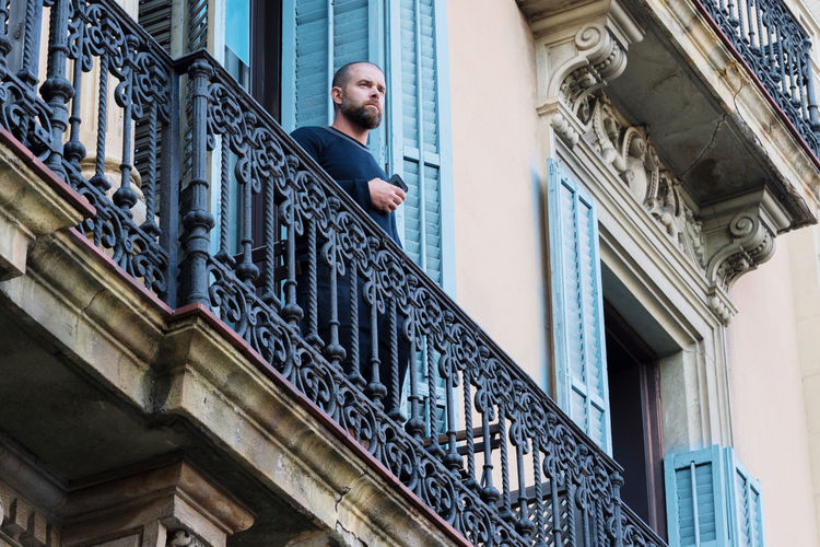 Man standing on the balcony on historical building holding his phone