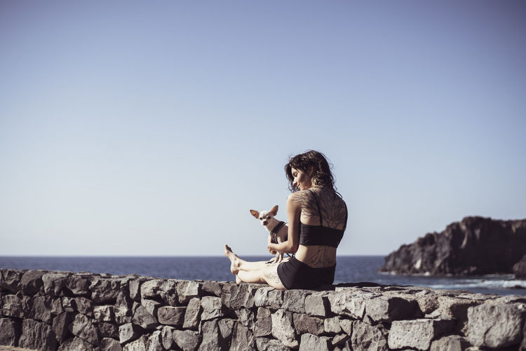 Young woman sitting on rock by sea against clear sky