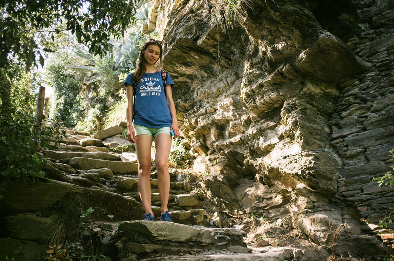 Young woman standing on stone steps
