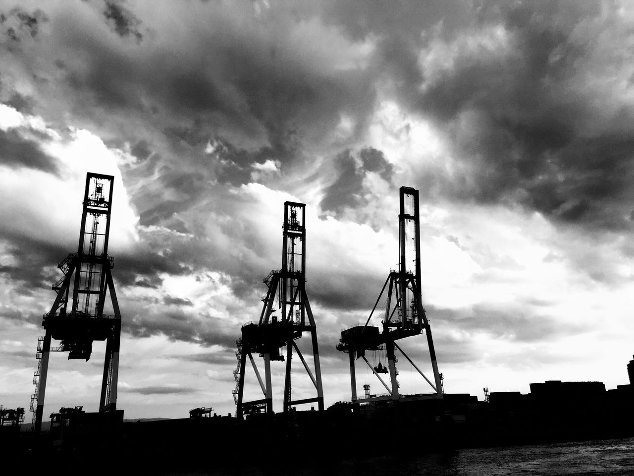Low Angle View Of Silhouette Cranes At Harbor