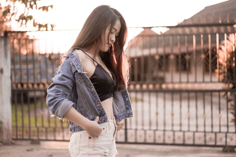 Seductive Woman Wearing Denim Jacket Standing In City During Sunset
