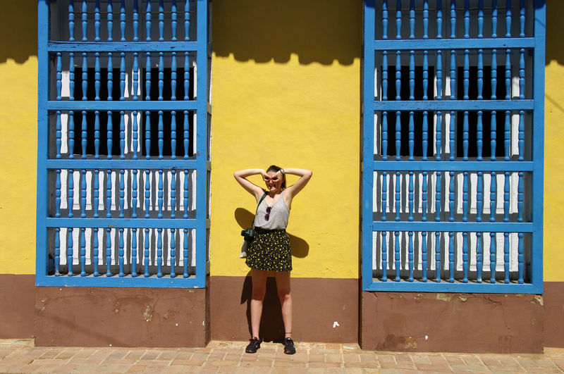 Full length of woman standing against yellow building