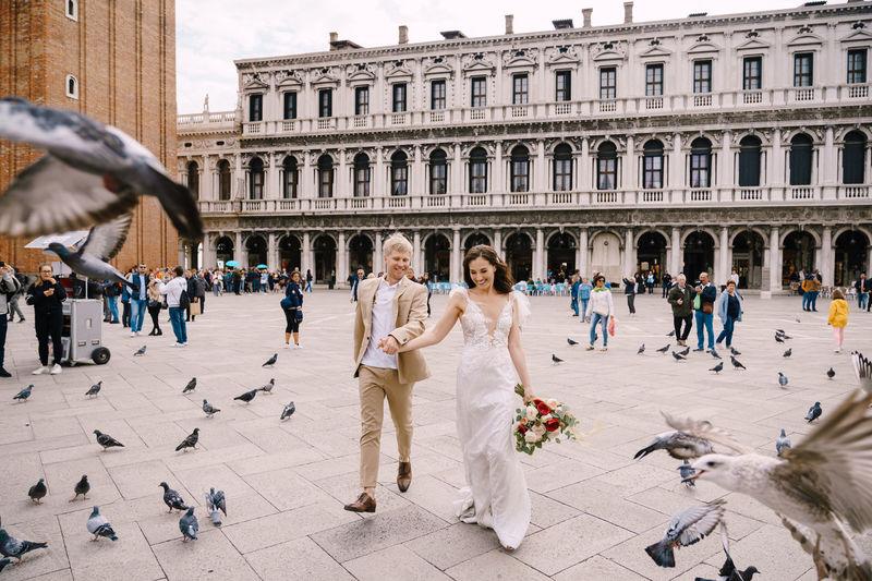 Full length of bridegroom holding hands walking against building