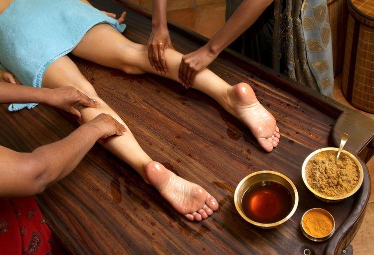 Cropped image of women massaging female customer leg at spa