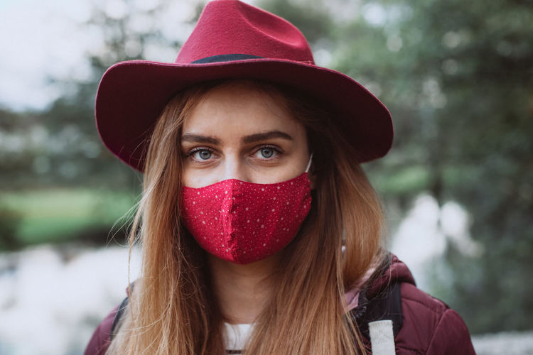 Portrait of beautiful young woman wearing hat with face mask