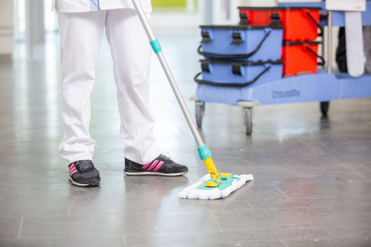 Worker cleaning up the floor in a hospital Body Part Broom Cleaning Cleaning Equipment Day Flooring Focus On Foreground Human Foot Human Leg Hygiene Indoors  Low Section Möp Occupation People Real People Service Standing