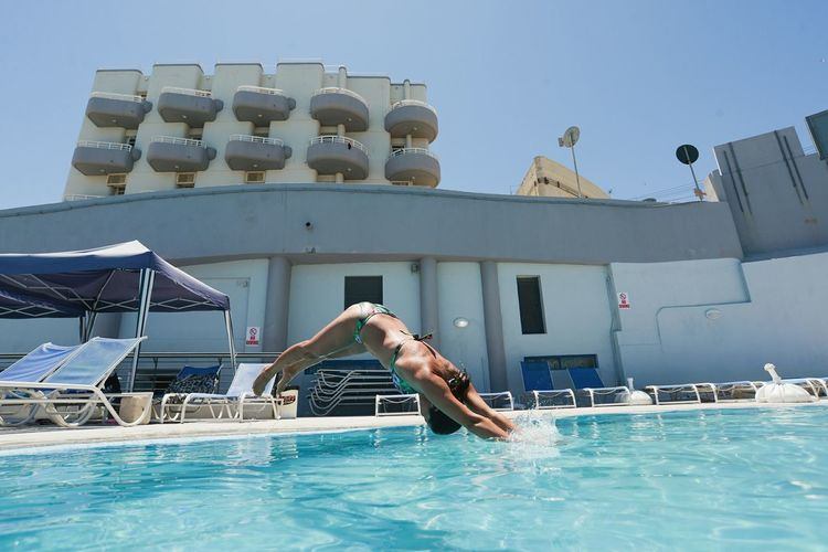 Young man swimming in pool against clear sky