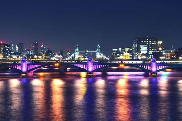 Illuminated bridge over river and buildings at night
